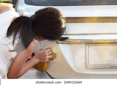 cute Southeast Asian Thai kid children sister teenager cleaning washing car in orange morning light with copy space, household helping concept