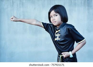 Cute sport girl practicing wushu (gongfu) , Chinese martial arts concept.
