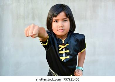 Cute sport girl practicing wushu (Kung fu , gongfu) , Chinese martial arts concept.