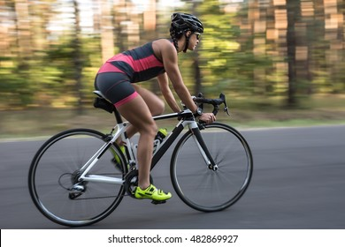 Cute sportive girl rides a bike on the road on the nature background. She wears black-pink sportswear, a stopwatch, a black helmet, sunglasses and green sneakers. Shoot from the side. Horizontal.