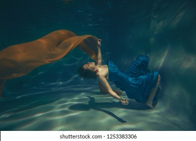 cute sporty female swims underwater as a free diver in a blue evening dress with orange fabric alone