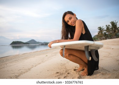cute sporty surfer girl or smiling happy brunette woman with surfboard relaxing, having rest on sunny beach near the ocean or sea. mountains, palms on background