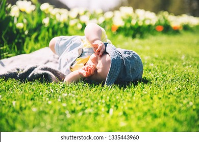 Cute squinting in the sun baby girl lying in green grass of tulip field. Child playing outdoors in spring park. Image of Mother's Day, Easter. Family on nature in Arboretum, Slovenia, Europe.