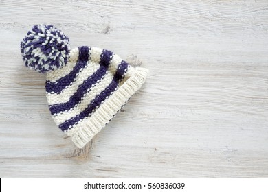 cute striped baby hat on wooden surface