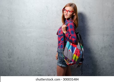 Cute student. Attractive young woman in plaid shirt holding backpack while standing against wall.