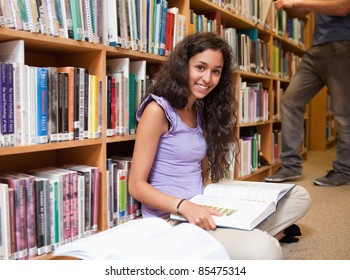 Cute student with a book in a library