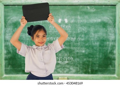 Cute student hold board in classroom