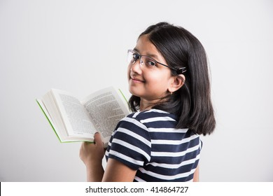 Cute and studious little Indian/asian girl studying/reading book while standing isolated over white background