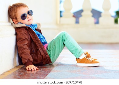 cute stylish boy in leather jacket and gum shoes