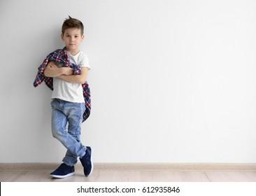 Cute stylish boy near light wall