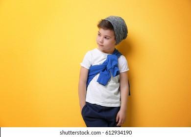 Cute stylish boy on color background