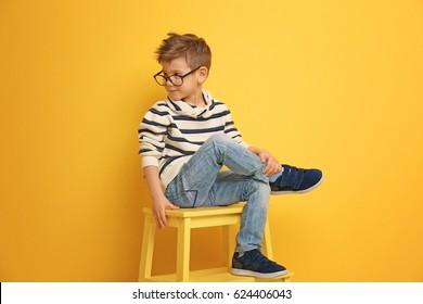 Cute stylish boy sitting on chair near color wall