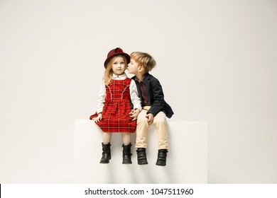 Cute stylish children on white studio background. Two beautiful teen girl and boy sittting together. Stylish young teen girl posing at studio. Classic style. Teen and kids fashion concept. children's