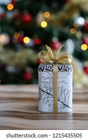 Cute and stylish Christmas present. The gift is on a wooden surface and there is a beautiful, colorful Christmas three with a lot of lights and decoration in the background. Warm and welcoming colors.