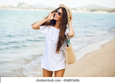 Cute stylish girl standing on a beach talking on a smartphone. Girl wears straw hat, beach straw bag and short white dress with open shoulders. She has brown sunglasses on. Ocean behind her.