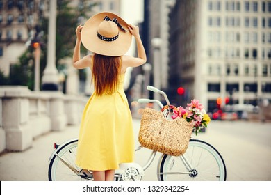 a cute and stylish girl in a yellow dress and long hair rides on a bicycle with a basket of flowers in the sunny summer city