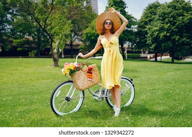 a cute and stylish girl in a yellow dress and long hair rides on a bicycle with a basket of flowers in the sunny summer park