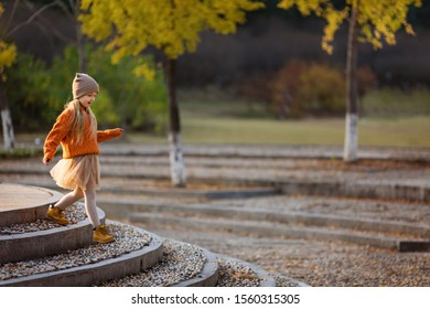 Cute stylish little girl walking in autumn park with ginkgo trees. Autumn kids fashion. Happy childhood. Lifestyle portrait