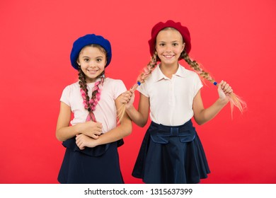 Cute and stylish. Little kids wearing stylish french berets. French style girls. Cute girls having the same hairstyle. Small children with long hair plaits. Fashion girls with tied hair into braids.