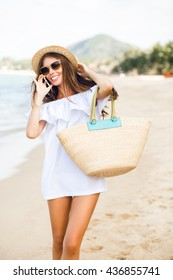 Cute stylish slim girl standing on a beach talking on a smartphone. Girl wears straw hat, beach straw bag and short white dress with open shoulders. She has brown sunglasses on.