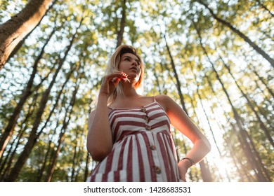 Cute stylish young blond woman in a pink fashionable striped sundress posing in the forest on a bright sunny summer day. Attractive girl likes to relax in nature. Bottom view.