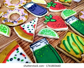 Cute sugar cookies decorated to look like strawberries, limes, avocado toast, drinks and pizza slices