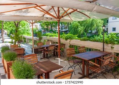 Agradable restaurante de verano en la terraza con vistas al río, rodeado de plantas verdes.