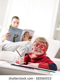 Cute superhero boy drawing with mother reading on background.