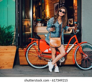 Cute surfer girl in a summer dress, denim jacket, sunglasses and bag stands with red vintage bicycle in LA city, California. Sunny summer. On background surf cafe. Outdoor.