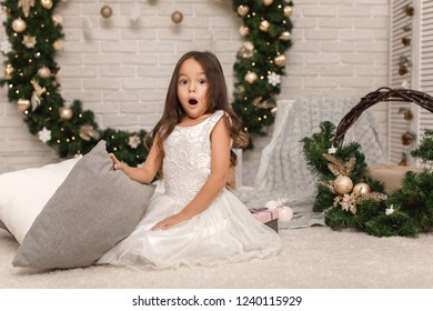 Cute surprised happy child girl on the background of the Christmas wreath at home.