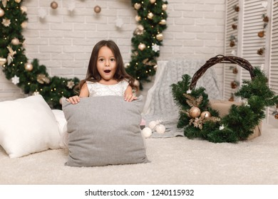 Cute surprised happy child girl on the background of the Christmas wreath at home. pillow as a place for text