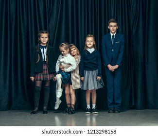 Cute surprised stylish children on dark background. Beautiful stylish teen girls and boy standing together and posing on the school stage in front of the curtain. Classic style. Kids fashion and