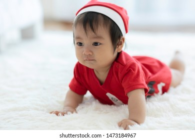 Cute Sweet Adorable Asian Baby wearing Santa hat and cloth costume lying on white carpet smiling and playing with happiness emotional in cozy bedroom,Healthy Baby Concept