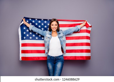 Cute sweet lovely confident smiling student lady emigrant holding USA american flag behind back, wearing casual jeans denim, isolated over grey background