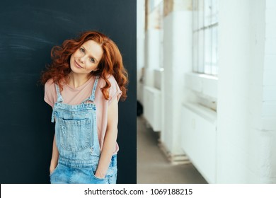 Cute sweet young woman with long red hair and a gentle smile standing with her hands in her denim dungarees indoors looking at the camera with tilted head
