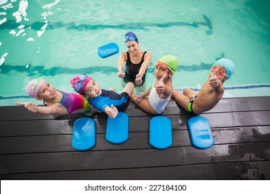 Cute swimming class and coach smiling at the leisure center