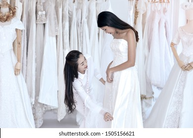 Cute Tailor check wedding dress size for beautiful Asian bride during dress fitting in taikoring room