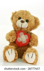 Cute teddy bear with decorative heart on bright background