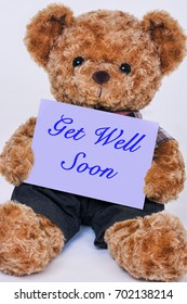 Cute teddy bear holding a purple sign that reads Get Well Soon isolated on a white background