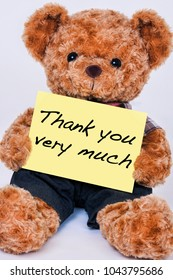 Cute teddy bear holding a yellow sign that says Thank you very much isolated on a white background
