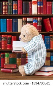 Cute teddy bear in nostalgic striped pajamas sitting on stack of books in front of bookshelf, reading at open book in his hands