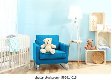 Cute teddy bear on blue armchair in baby room