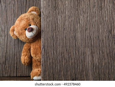 Cute teddy bear on old wood background with copy space