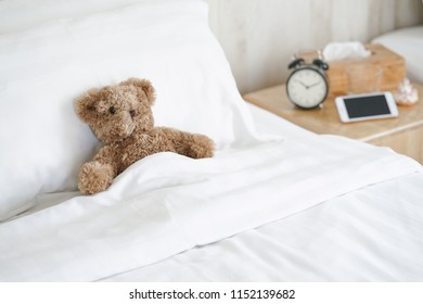 Cute teddy bear sleeping comfortably in bed, good morning and welcome a new day concept, soft focus