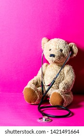 cute teddy bear with a stethoscope for child medical education and healthcare learning over pink copy space background