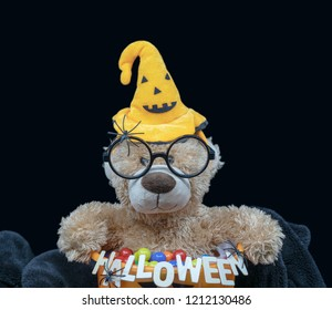 Cute teddy bear wearing black round glasses and Jack hat sitting inside orange pumpkin bucket full of candies with soft black blanket underneath. Isolated with dark background color with copy space on