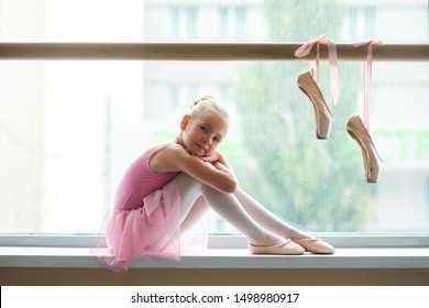 Cute teen ballerina sitting on windowsill. Lovely ballet girl in pink leotard. Pair of pointe shoes hanging on ballet barre.