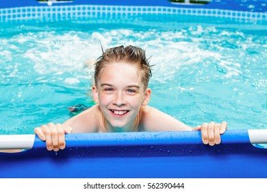 Cute teen boy enjoying summertime in a pool