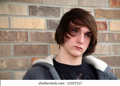 cute teen boy with great hair by brick wall