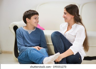 Cute teen boy with his young mother at home